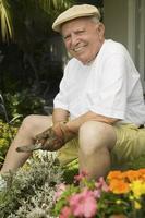 äldre man trädgårdsskötsel foto