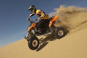 man ridning på fyrhjuling i öknen foto