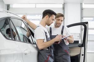 bilmekanik som kontrollerar checklistan när du står med bil i verkstaden foto