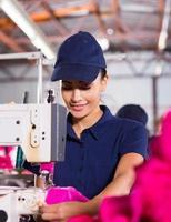 kvinnlig fabriksarbetare som sy plagg foto
