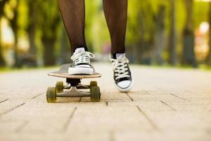 kvinnliga fötter på skateboard foto