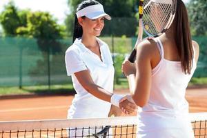 kvinnliga tennisspelare skakar hand foto