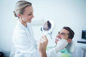 kvinnlig tandläkare som borstar mans tänder foto