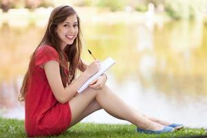 kvinnlig student med arbetsbok utomhus foto