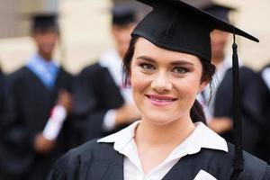 glad kvinnlig examen vid examen foto