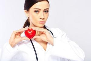 kvinnlig läkare som håller ett hjärta foto