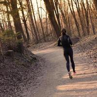 kvinnlig löpare i skogen.