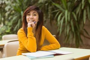 kvinnlig högskolestudent som gör läxor foto