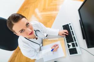 kvinnlig läkare skriver i dokument foto