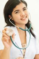 glad kvinnlig läkare som håller ut stetoskop foto