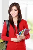 vacker kvinnlig student med leende böcker foto