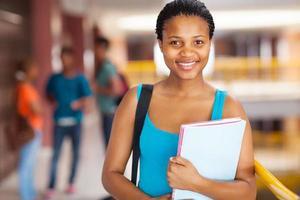 kvinnlig afrikansk högskolestudent som håller böcker foto