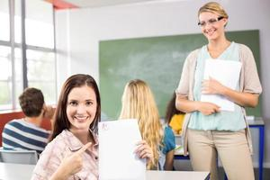 vacker kvinnlig student som pekar på papper foto