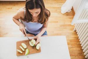 ungt kvinnligt skärande äpple. Bild från ovan. foto