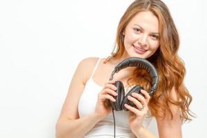 glad kvinna håller hörlurar runt halsen foto