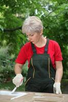 kvinnlig arbetare som återställer gammal trädörr foto