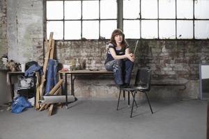 kvinnlig konstnär med pensel i verkstad foto
