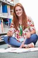 kvinnlig högskolestudent som studerar i biblioteket foto