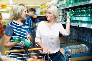 kvinnliga kunder som köper vatten på stormarknad foto