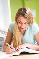 kvinnlig student som gör läxor i biblioteket foto