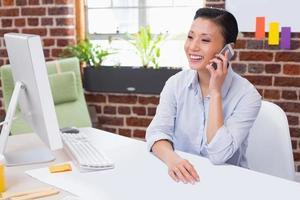 kvinnlig chef som använder mobiltelefonen vid skrivbordet foto