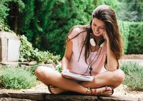 ung vacker kvinna sitter utanför och studerar. foto