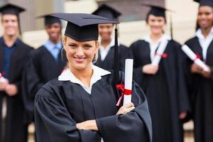 kvinnlig högskoleexamen med korsade armar foto