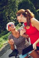 två unga kvinnor som har kul i parken foto