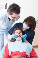 kvinnlig tandläkare och assistent som undersöker perfekta tänder foto