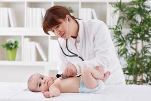 unga läkare kvinnliga undersöker en baby patient foto