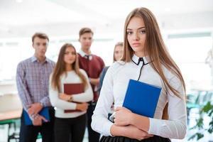 kvinnlig student som står med klasskamrater på bakgrund foto