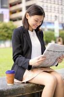 ung kvinnlig asiatisk företagsledare som läser tidningen