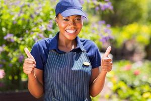 afrikansk kvinnlig plantskolearbetare med tummen upp foto