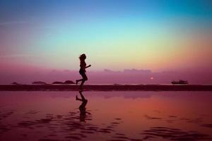 kvinnlig löpare på stranden vid solnedgången foto