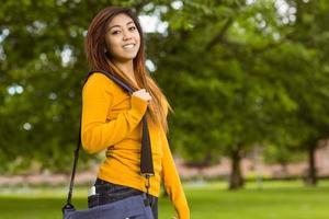 kvinnlig högskolestudent med väska i parken foto
