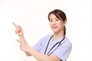 japansk kvinnlig läkare som presenterar och visar något foto