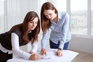kvinnliga arkitekter som studerar ritningar och gör anteckningar foto