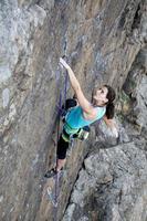 kvinnlig bergsklättrare som hänger över avgrunden foto