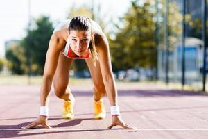 kvinnlig sprinter redo för körningen foto