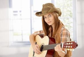 ung kvinna som spelar gitarr i västerländsk stil foto