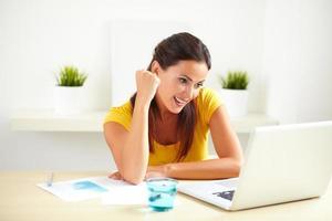 latinamerikanska kvinnliga anställd firar på sitt kontor foto