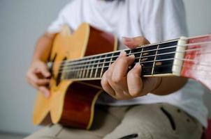 kvinnlig hand som spelar musik av akustisk gitarr foto