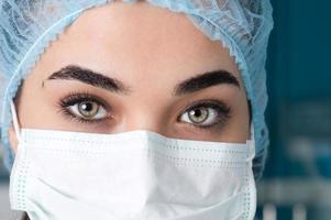 ung kvinnlig läkare i medicinsk mask, närbild foto