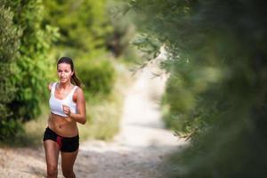 vacker ung kvinnlig löpare på en skogsstig foto