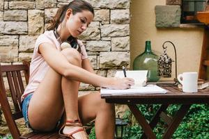 ung vacker kvinna sitter utanför och studerar hårt.