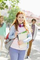 porträtt av ung kvinnlig student med vänner foto