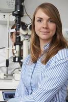 kvinnlig optiker som ger manlig klient ögonundersökning foto