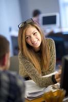 ung kvinnlig kontorsarbetare som pratar med kollega foto