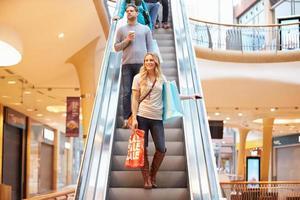 kvinnlig shoppare på rulltrappa i köpcentret