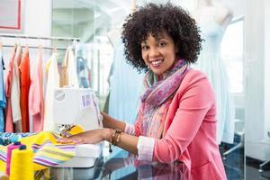 kvinnlig modedesigner med symaskin foto